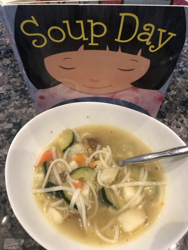 Cooking activities for toddlers inspired by books: Soup Day book with bowl of vegetable soup.