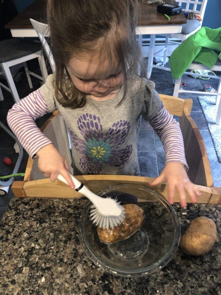 Toddler scrubbing potatoes.