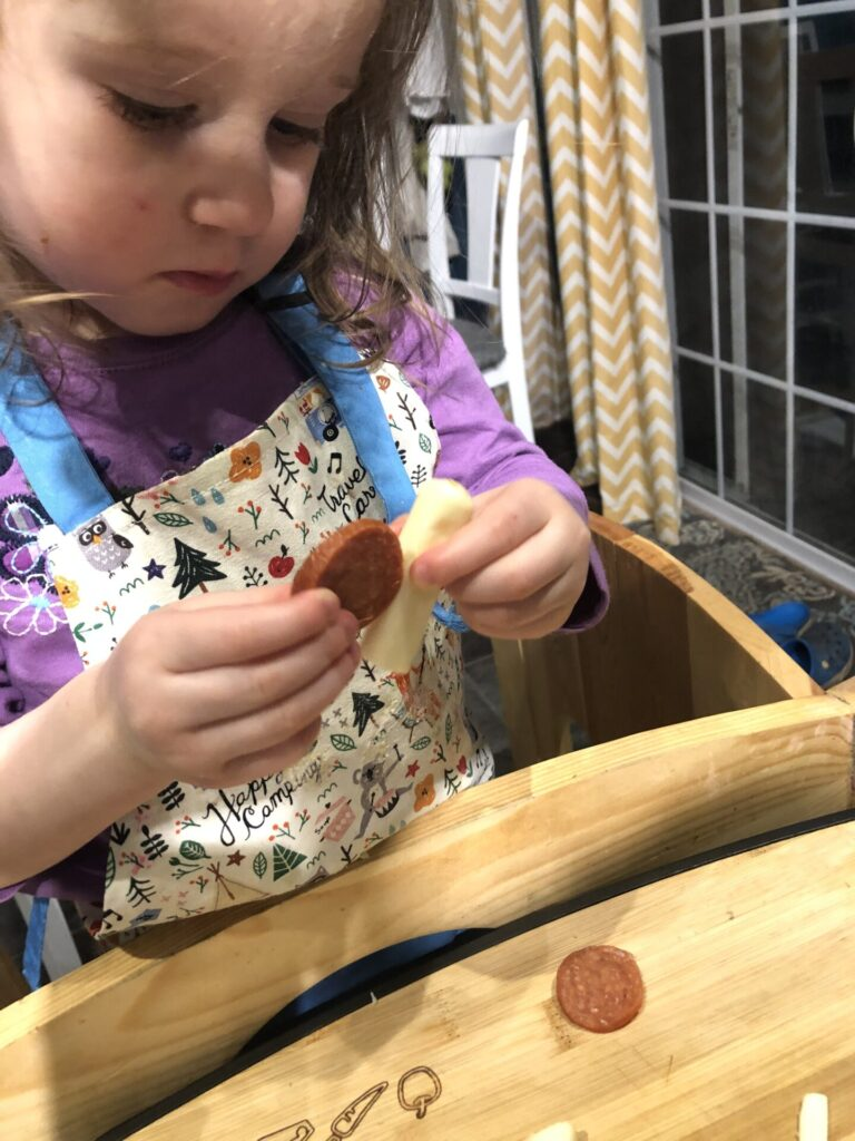 Toddler assembling snails from mozzarella sticks and pepperoni for snail pizza cooking activity.