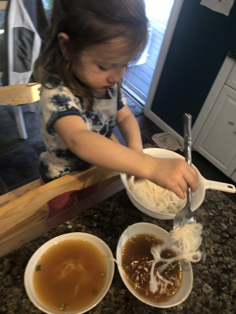 Cooking activities for toddlers: girl putting Noodles in wonton soup for dim sum.