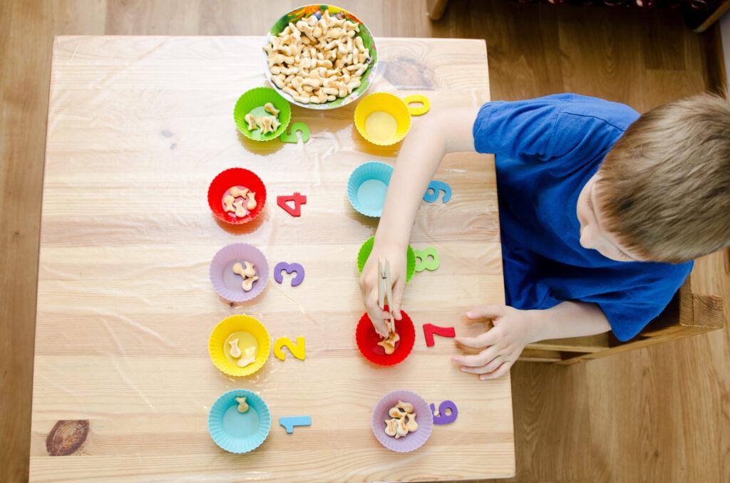 child using Godlfish crackers for Montessori math activity.