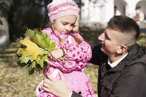 father showinf posisitve discipline to child holding flowers.
