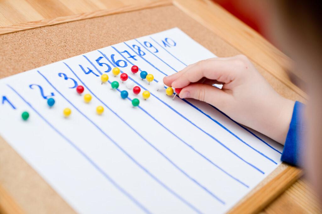 child using push pins for 1:1 correspondence Montessori math activity.