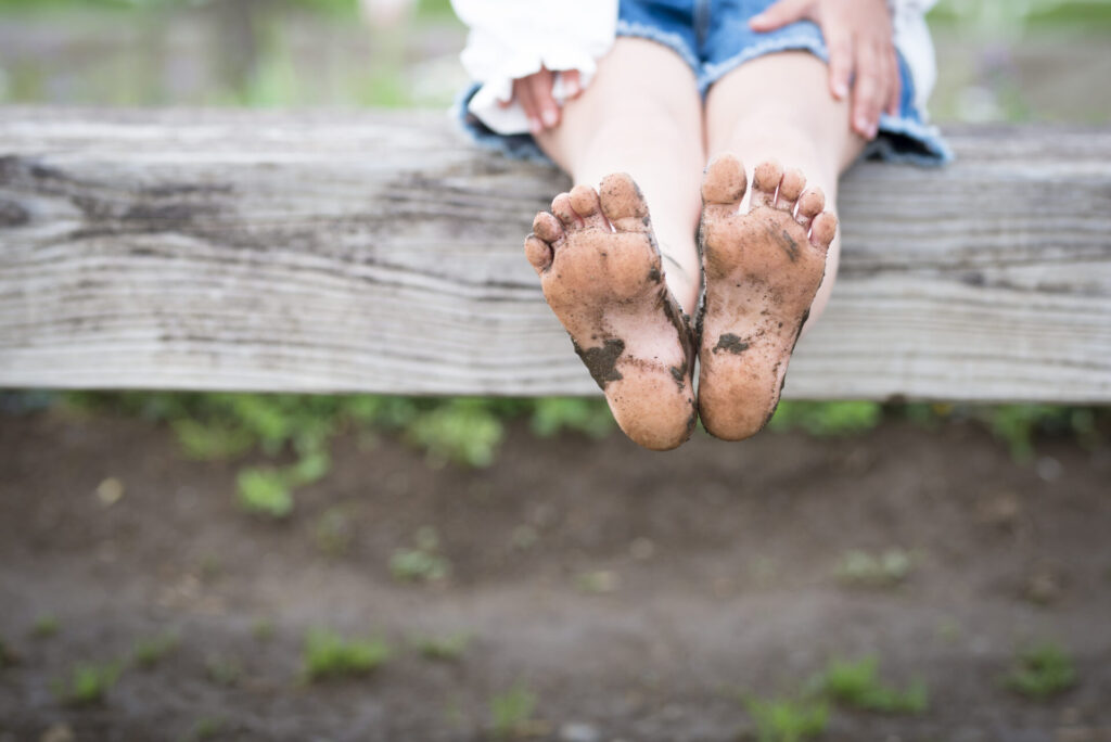 child outside with dirty feet.
