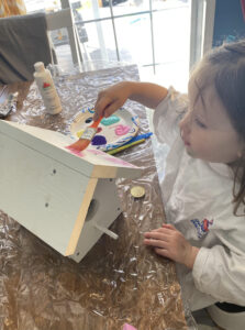 toddler painting diy wooden birdhouse with father.