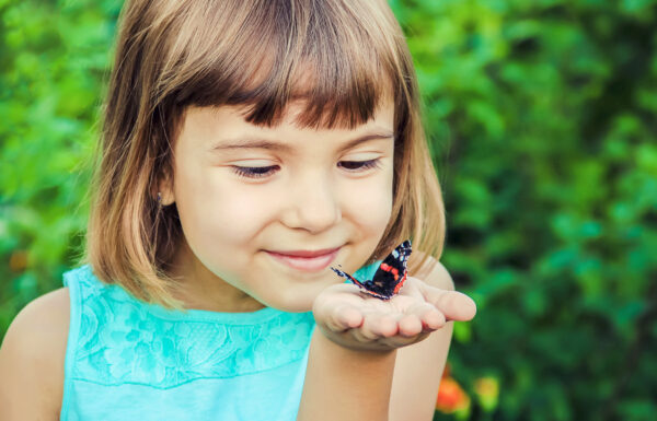 child holding butterfly.