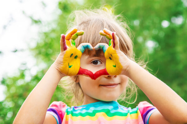 image of child making heart with hands with items from Montessori subscription boxes.