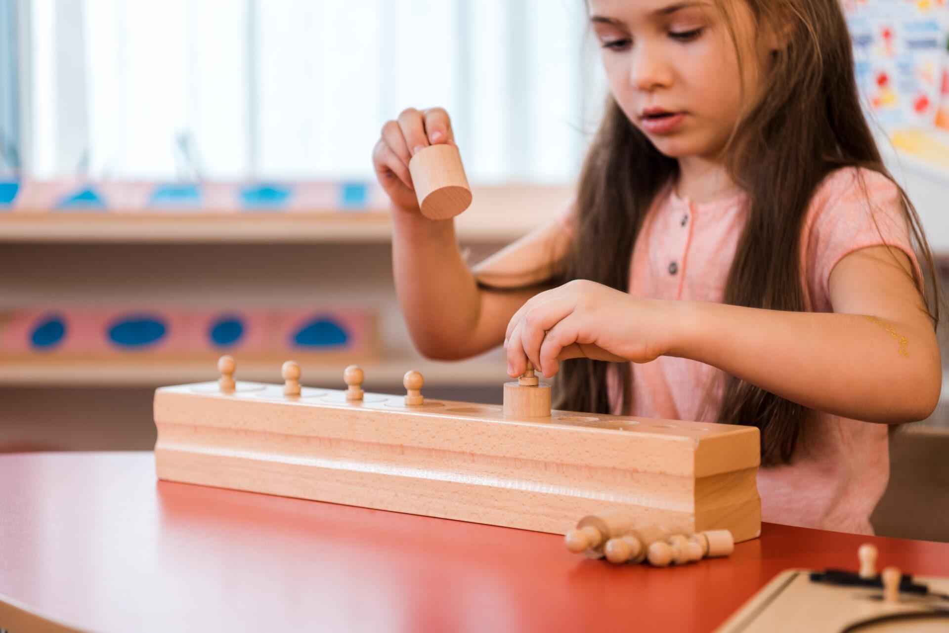 image of girl using montessori knobbed cylinders.