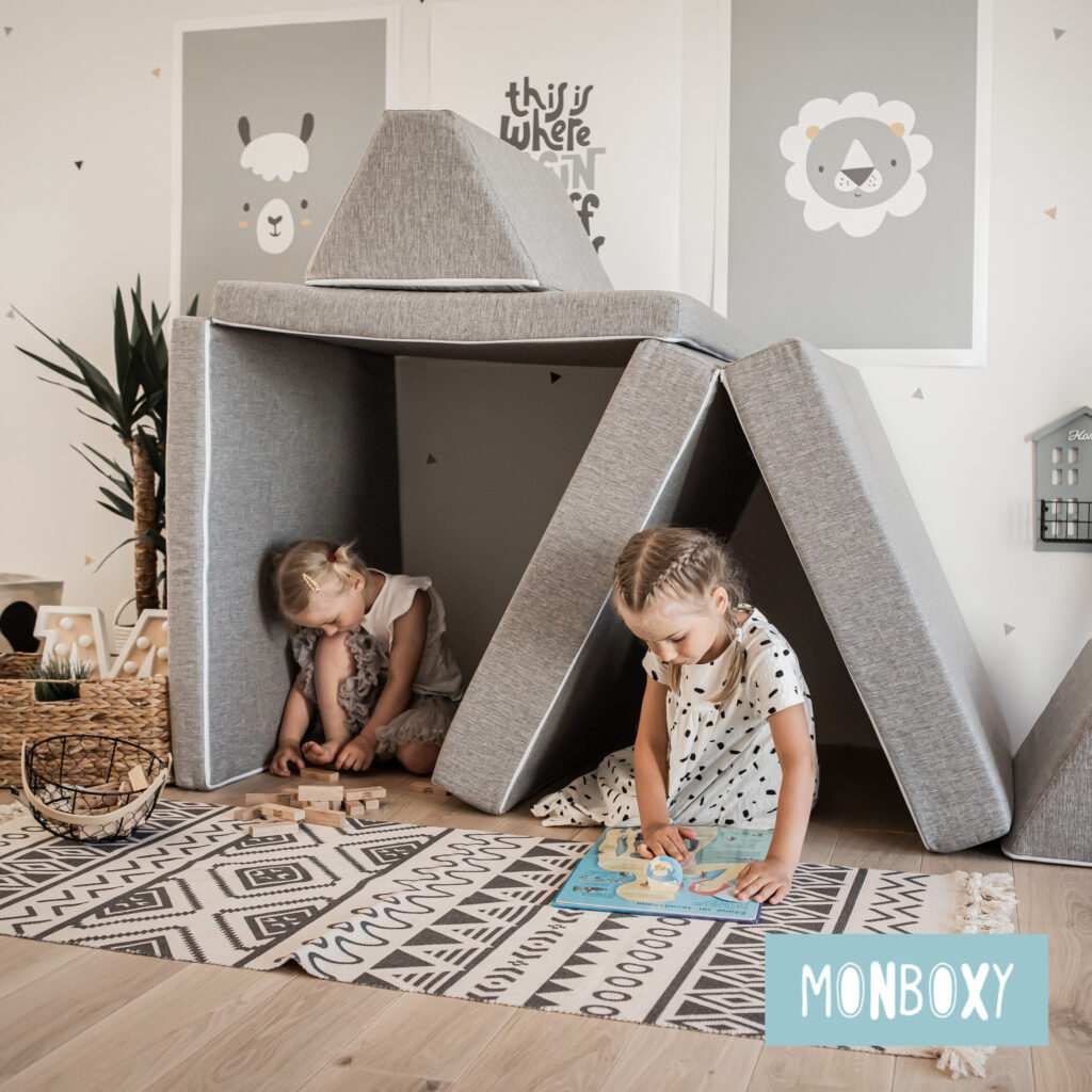 image of monboxy gross motor foam couch with 2 children underneath.