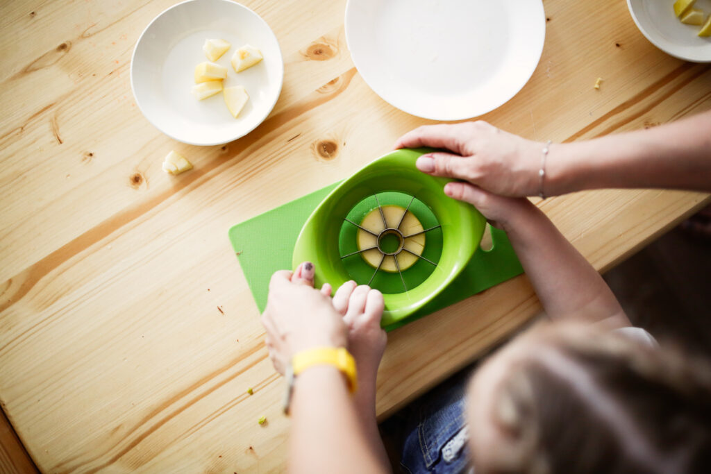 image of child cutting an apple when doing Montessori at home.