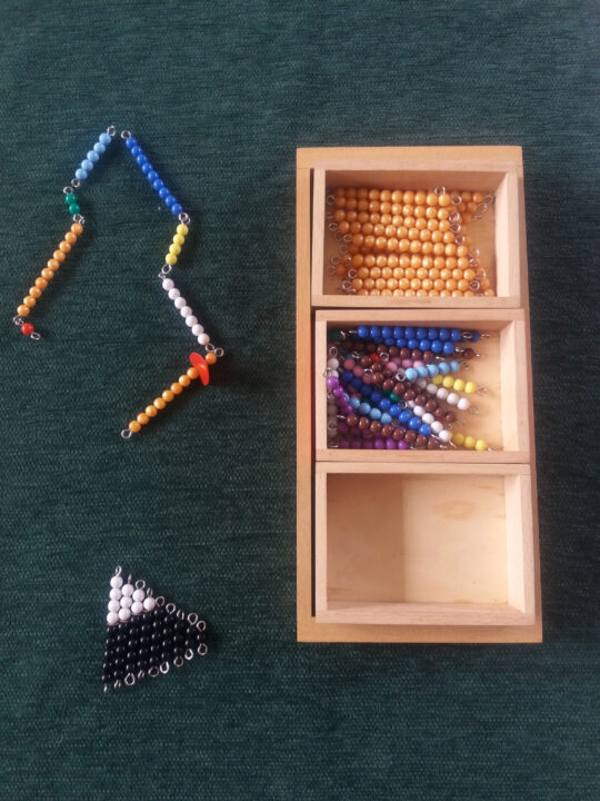image of colored bead bars laid out for Montessori Snake Game.