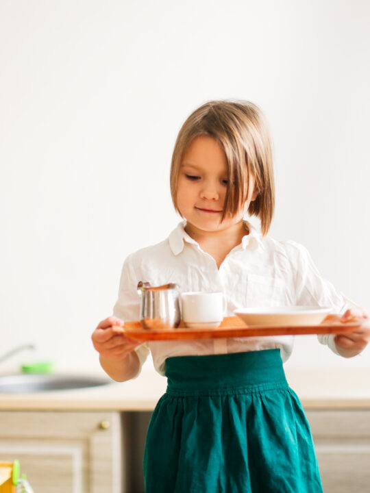 image of a child carrying a tray in Montessori.