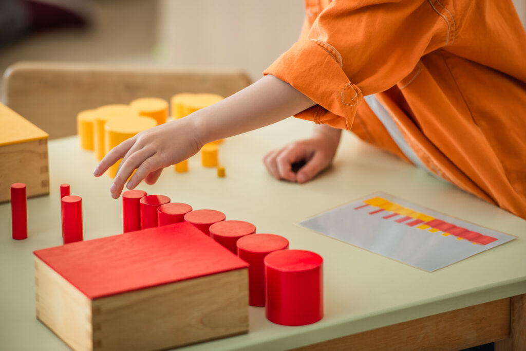 image of a child working with the Montessori knobless cylinders.