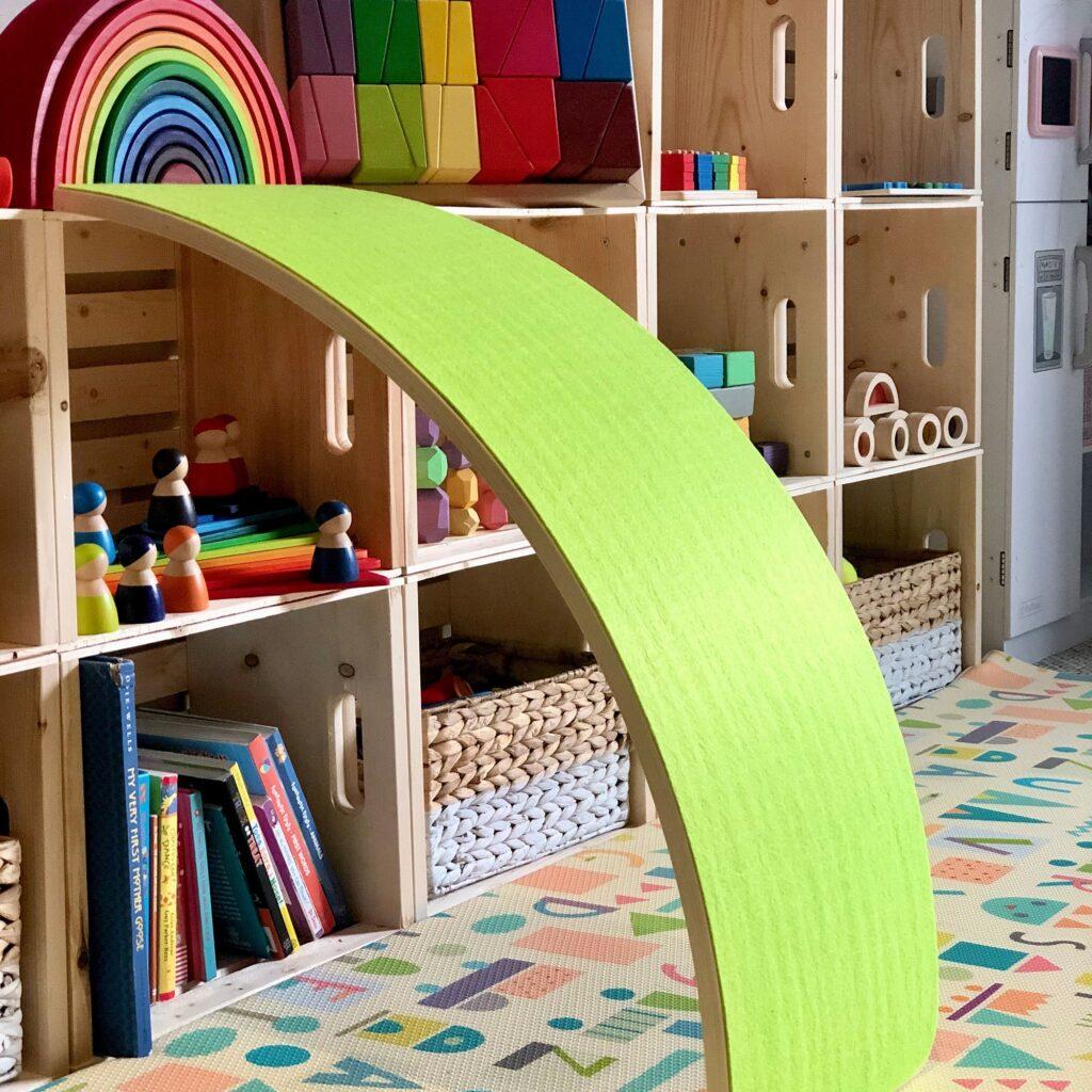 image of green walnut balance board. against toy shelf.