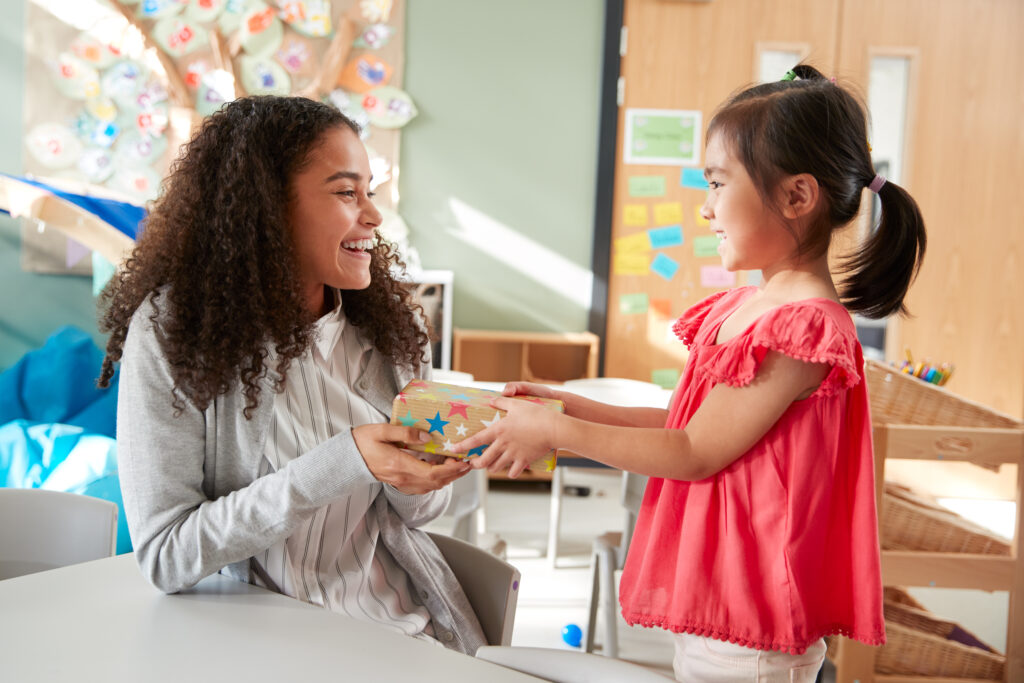 image of a child giving a montessori teacher a gift.