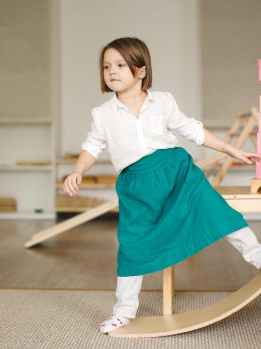 image of a child playing on a montessori balance board.